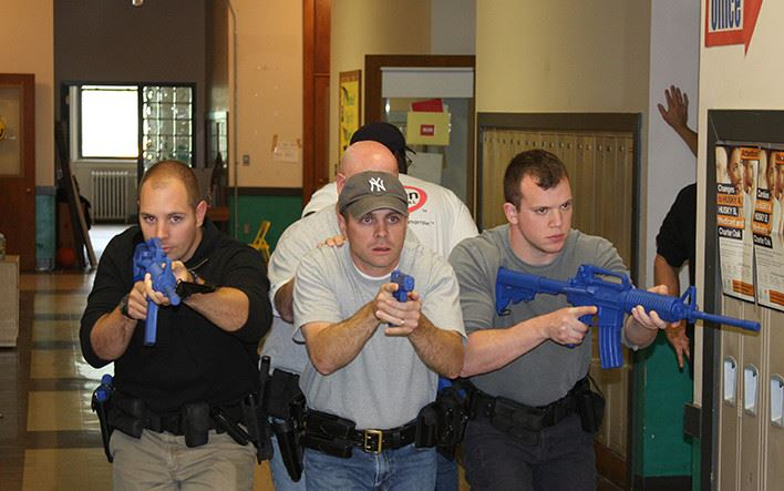 a group of policemen going through a drill with plastic guns